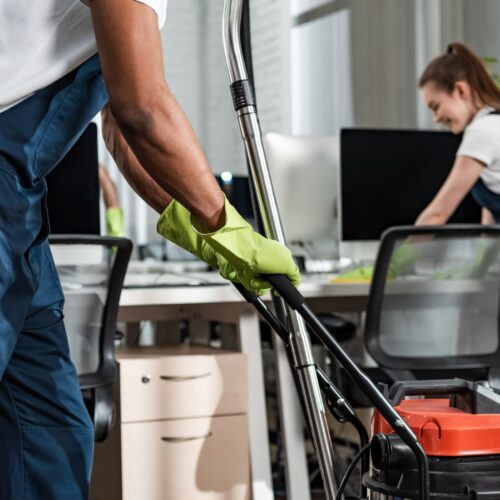 cropped view of african american cleaner moving vacuum cleaner in office
